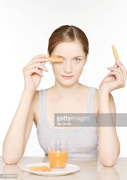 Young woman with carrot sticks and carrot juice