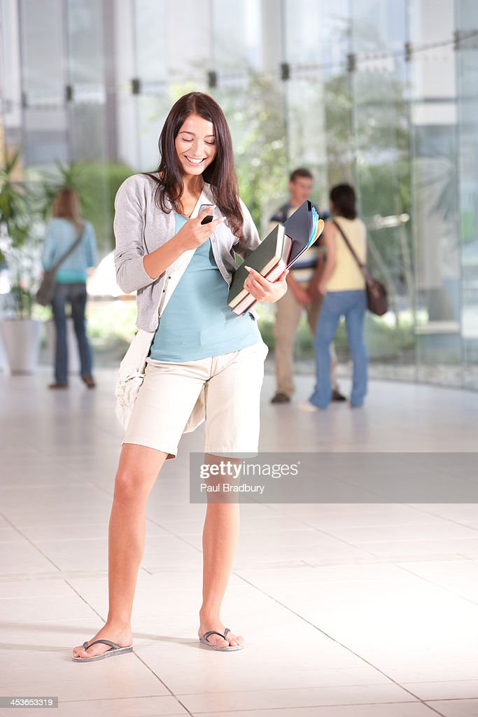 Young Woman with cell phone and books at school