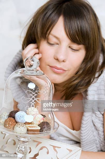 Young woman with chocolates under a glass dome