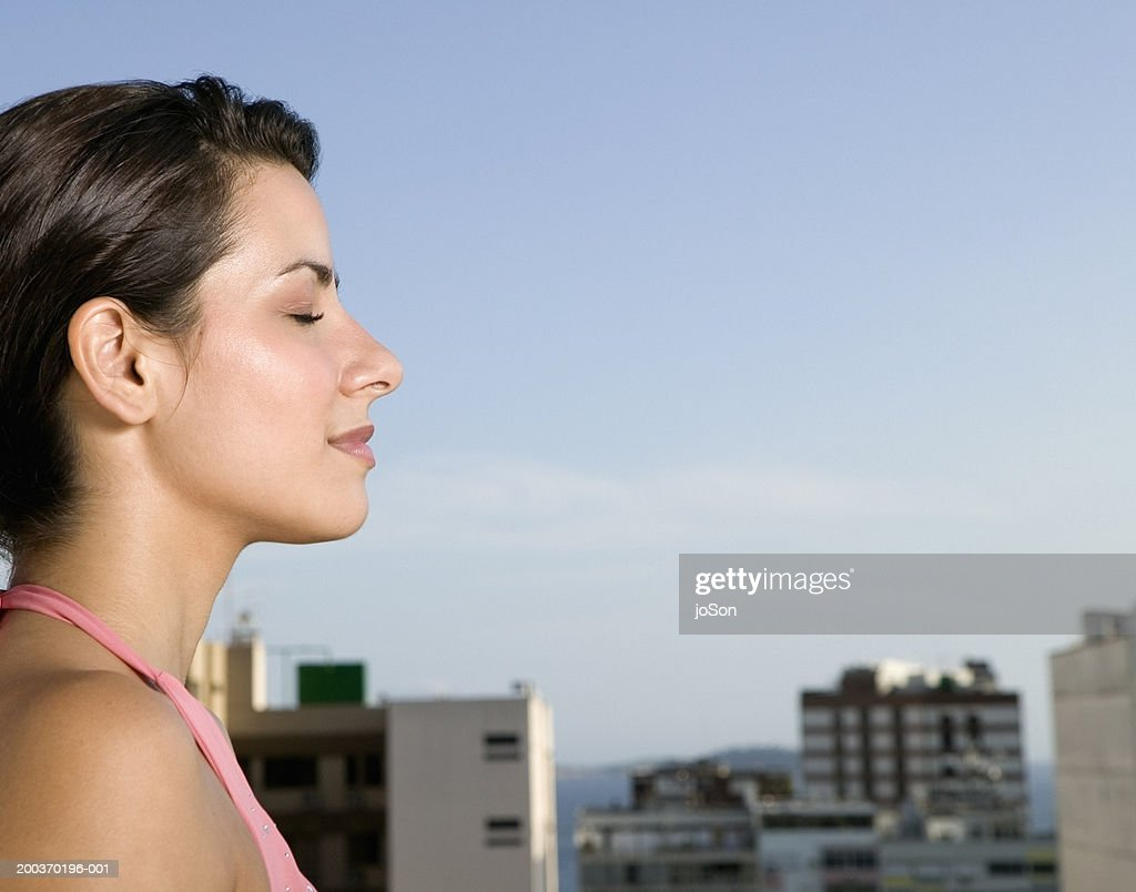 Young woman with city skyline in background, eyes closed, side view : Stock Photo