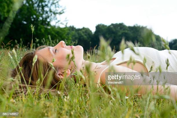 Young woman with closed eyes lying on a meadow