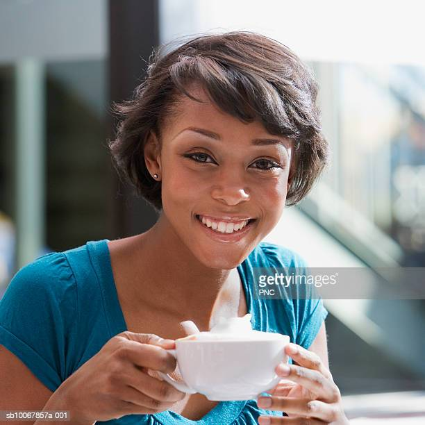 Young woman with coffee at a cafe, portrait