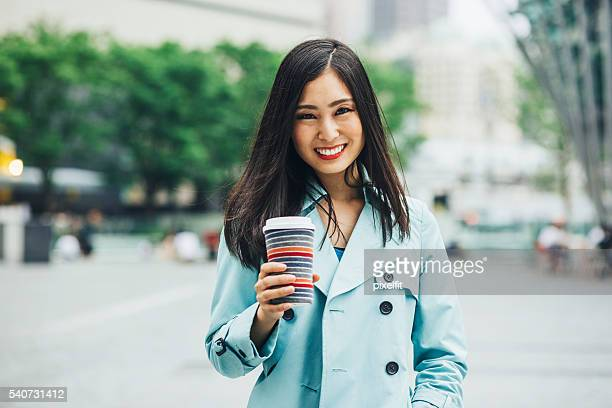 Young woman with coffee cup on the street