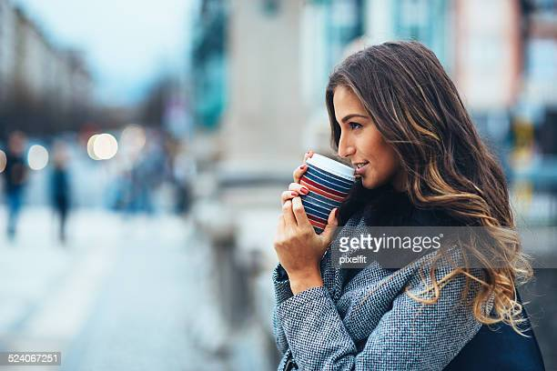Young woman with coffee cup outdoors
