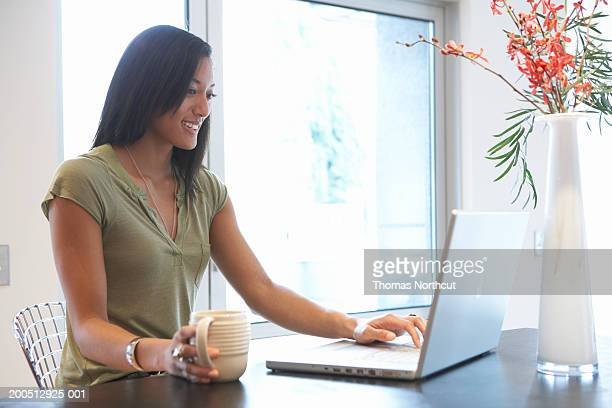 Young woman with coffee cup using laptop, smiling