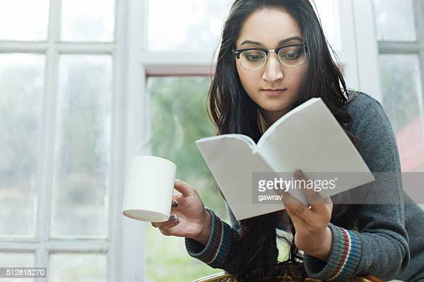 Young woman with coffee mug and book, studying near window.