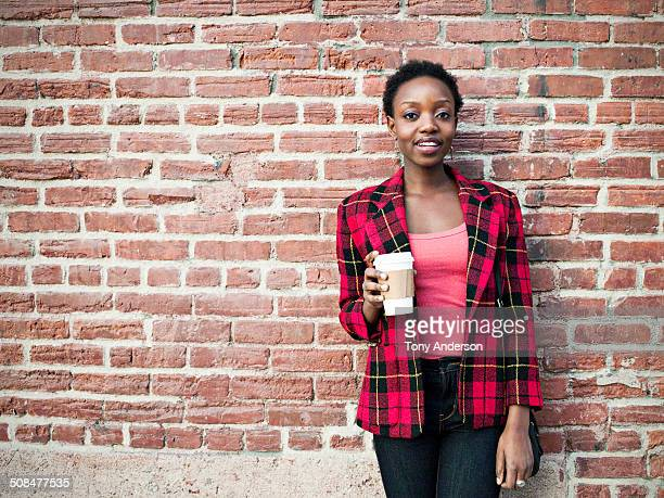 Young woman with coffee on city street