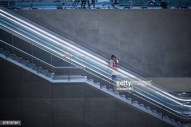 Young woman with coffee to go standing on escalator