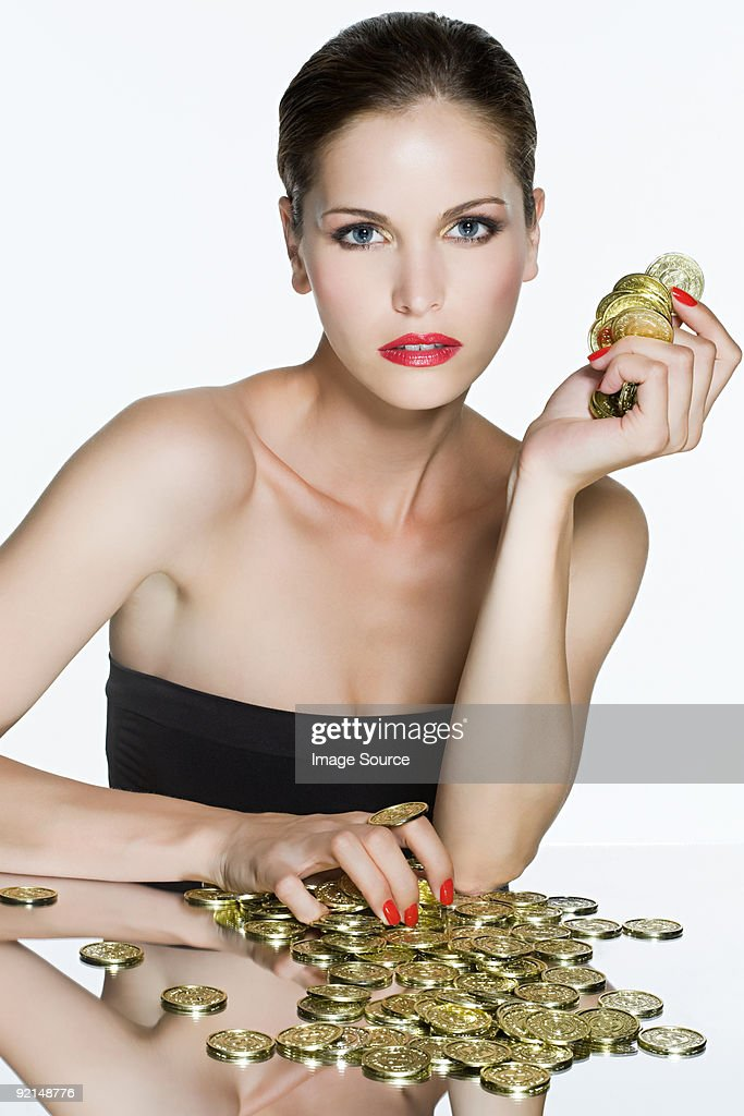 Young woman with coins : Stock Photo
