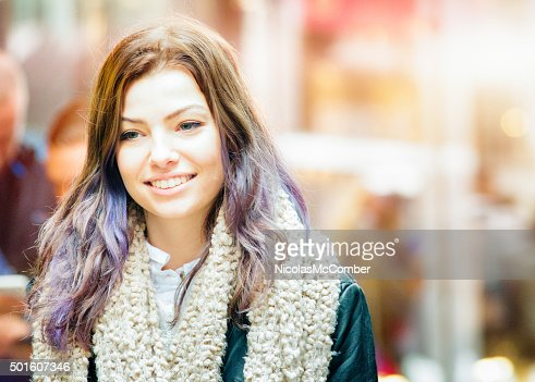 Young woman with colorful hair smiling as she walks