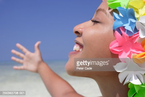 Young woman with colorful shower cap on beach, eyes closed, smiling
