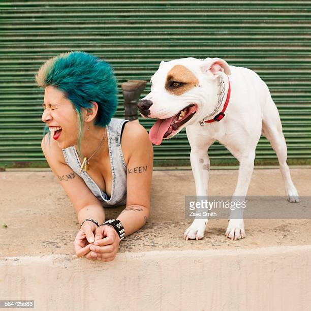 Young woman with colourful hair, lying on floor next to dog, laughing
