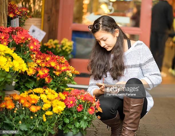 Jeune femme avec ordinateur tablette dans un magasin de fleurs
