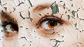 Beauty and health concept - face covered with cracked surface - symbol of dry skin and stress