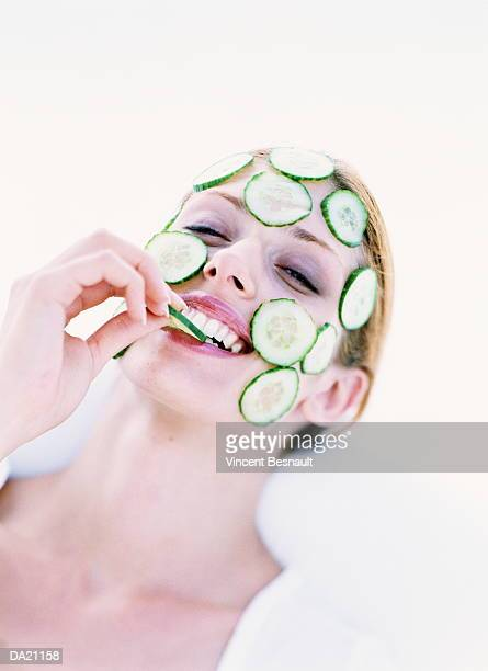 Young woman with cucmber slices on face, nibbling slice of cucumber