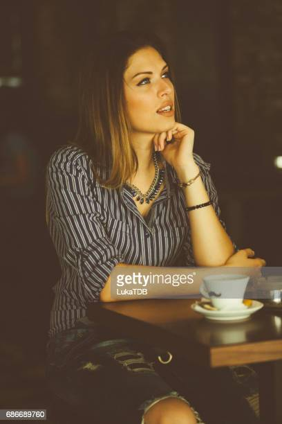 Young woman with cup of coffee at the bar