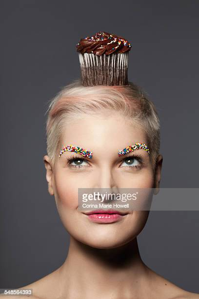 Young woman with cupcake on top of head
