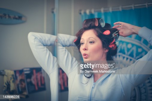 Young woman with curlers in bathroom singing
