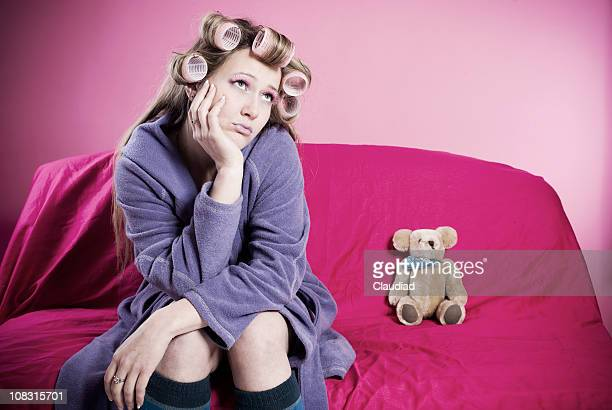 Young woman with curlers sitting on couch
