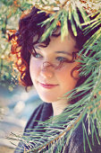 Young woman with curly red hair amid branches