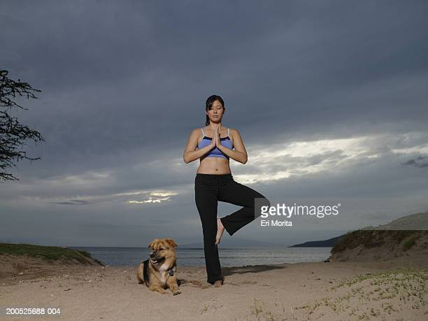 Young woman with dog practicing yoga at beach, dusk