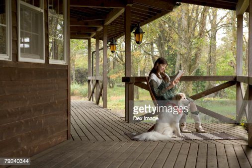 Young woman with dog, reading at the porch : Stock Photo