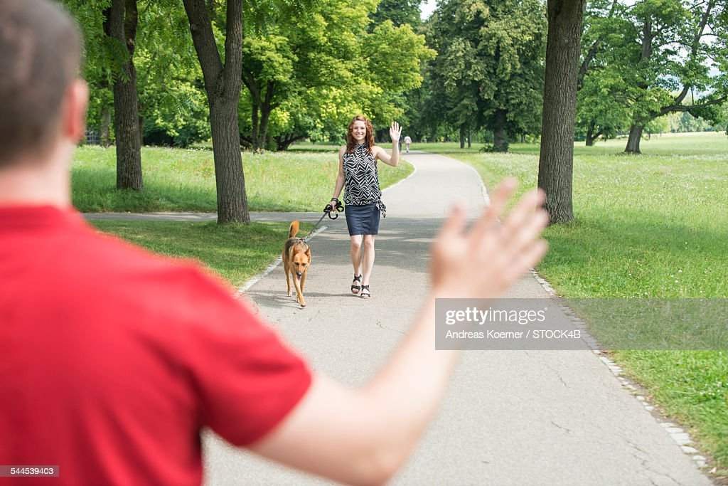 Young woman with dog waving to man in park