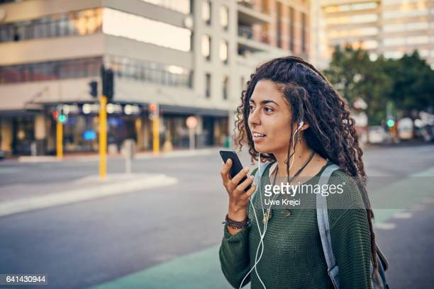 Young woman with dreadlocks talking on her smart phone