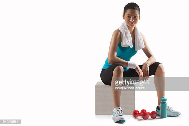 Young woman with dumbbells sitting on stool isolated over white background