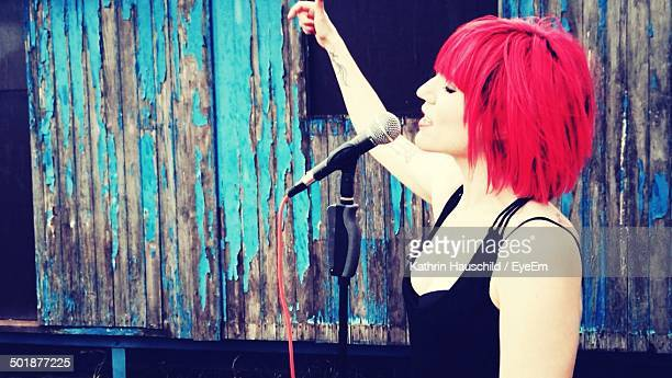 Young woman with dyed hair singing into microphone