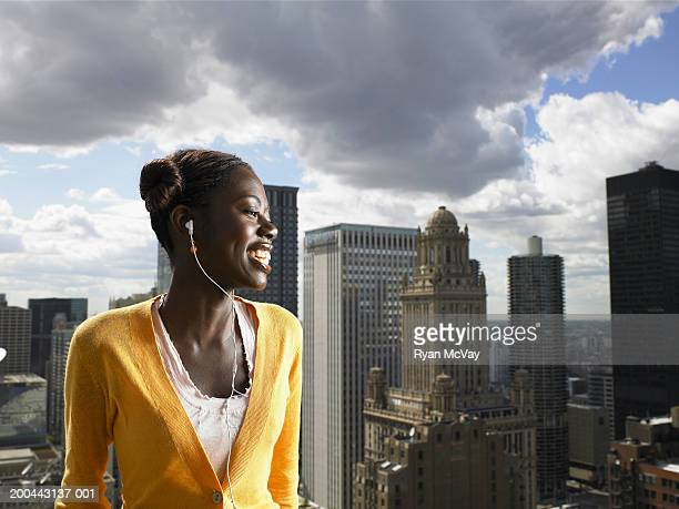 Young woman with earphones standing on rooftop