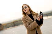 Portrait of young woman with eyeglasses with mobile phone outdoor