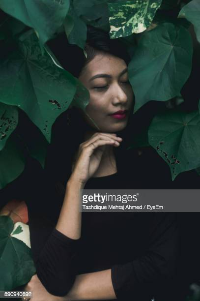 Young Woman With Eyes Closed Standing Against Tree
