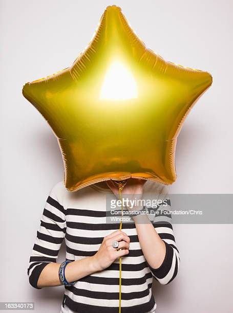Young woman with face covered by balloon