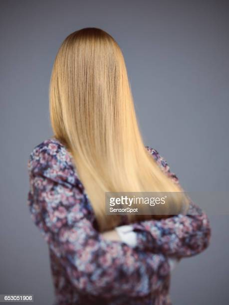 Young woman with face covered by long blonde hair