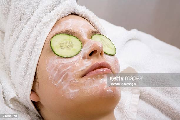 Young woman with face mask and cucumber slices, close-up