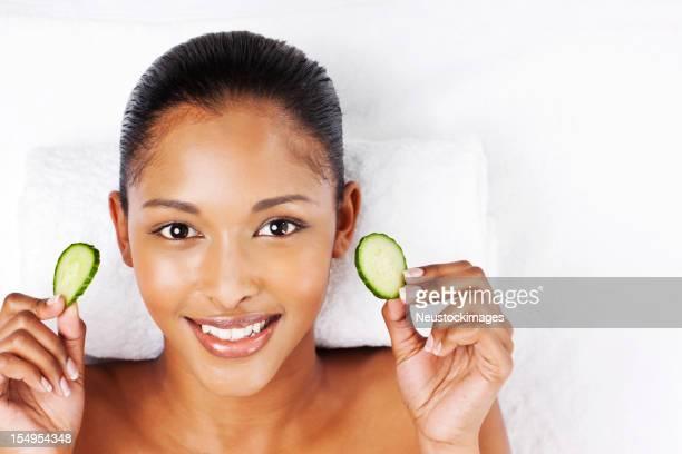 Junge Frau mit Gesichtsmaske Gurken