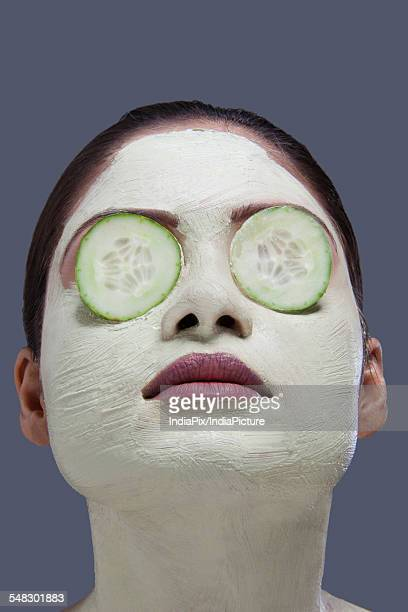 Young woman with facial mask and cucumber over her eyes