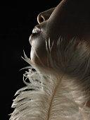 Mujer joven con la pluma en la barbilla, vista lateral close-up