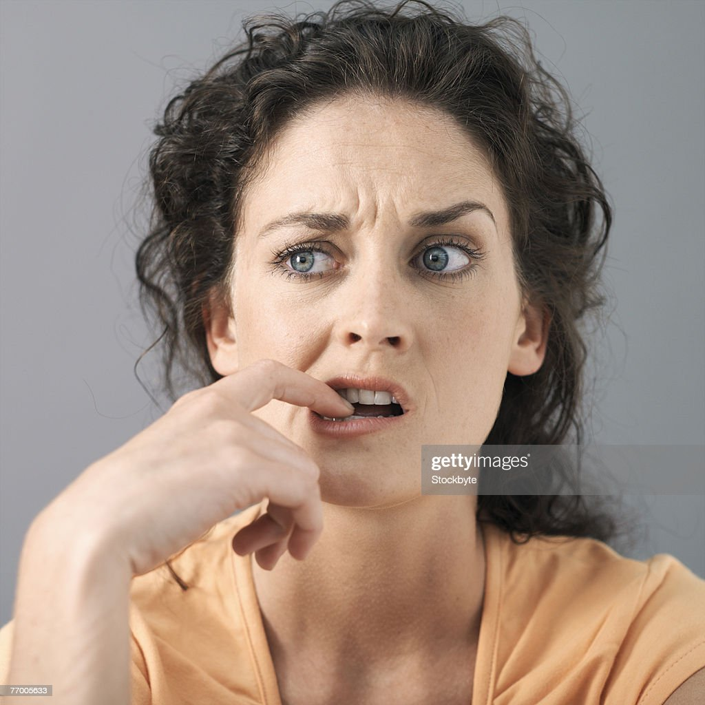 Young woman with finger in mouth, close-up, studio shot : Stock Photo