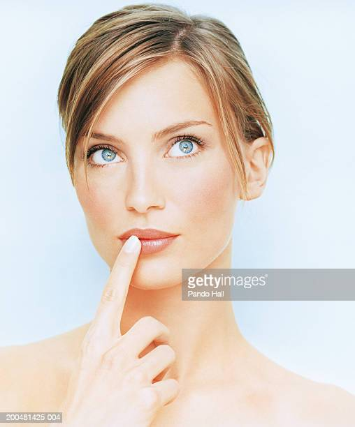 Young woman with finger on lip, looking up, close-up