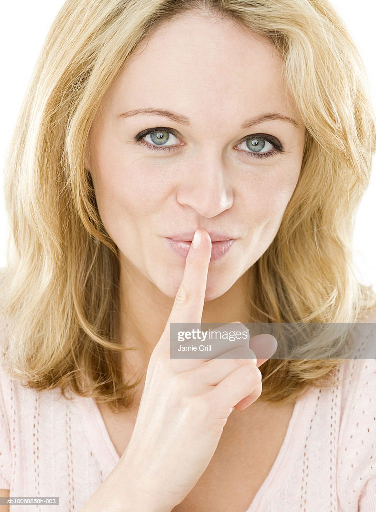 Young woman with finger on lips, close-up, portrait : Stock Photo