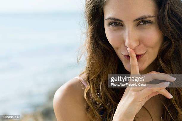 Young woman with finger on lips, portrait