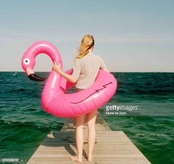 Young woman with flamingo ring on pier