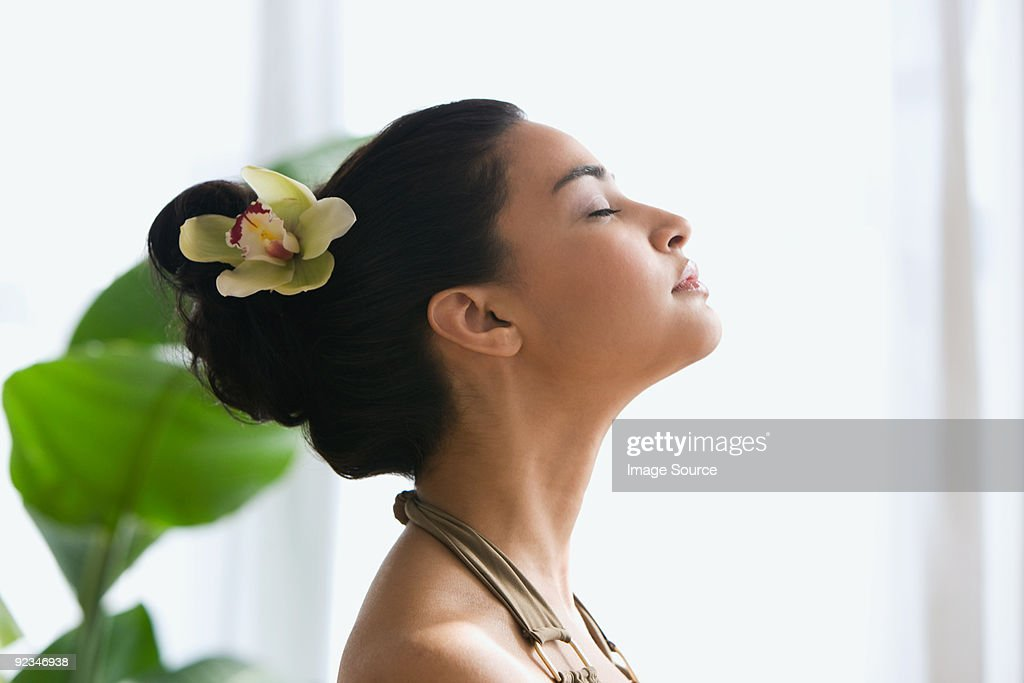 Young woman with flower in hair : Stock Photo