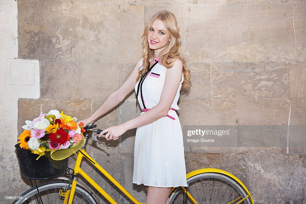 Young woman with flowers in basket of bicycle : Stock Photo
