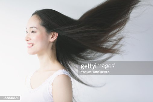 Young woman with fluttering hair smiling