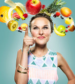 Young woman with flying fruits around her head, Composite