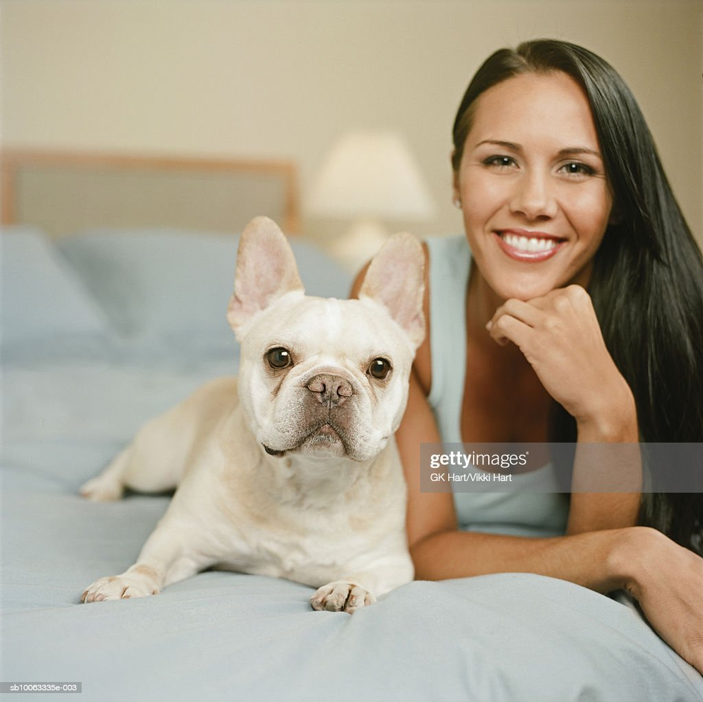 Young woman with French Bulldog lying on bed, smiling, portrait : Stock Photo