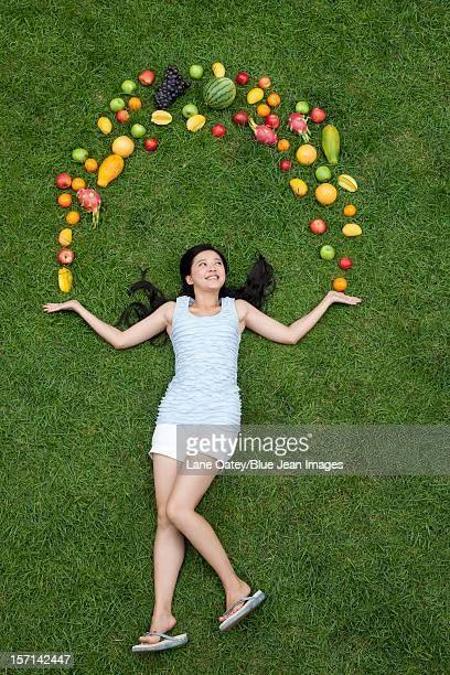 Young woman with fresh fruits on meadow